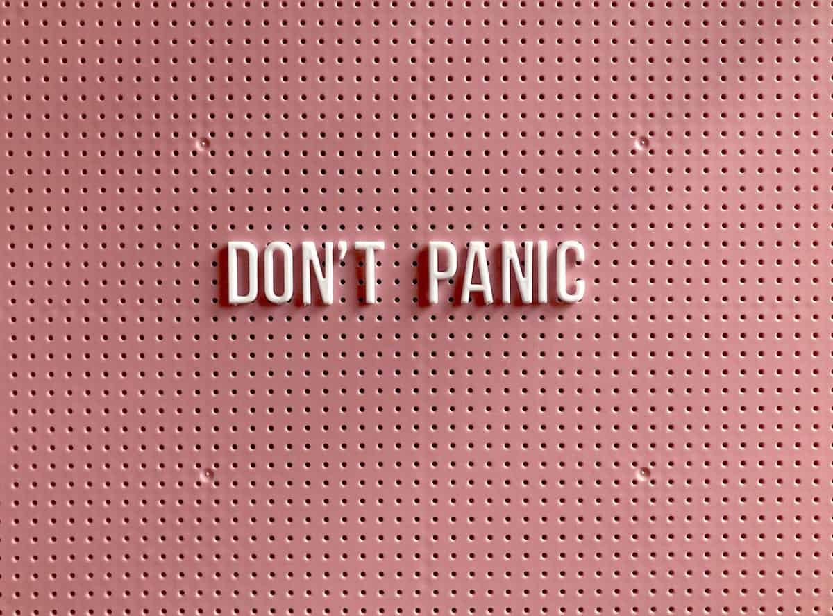 """A pink background with white letters that say """"don't panic""""."""