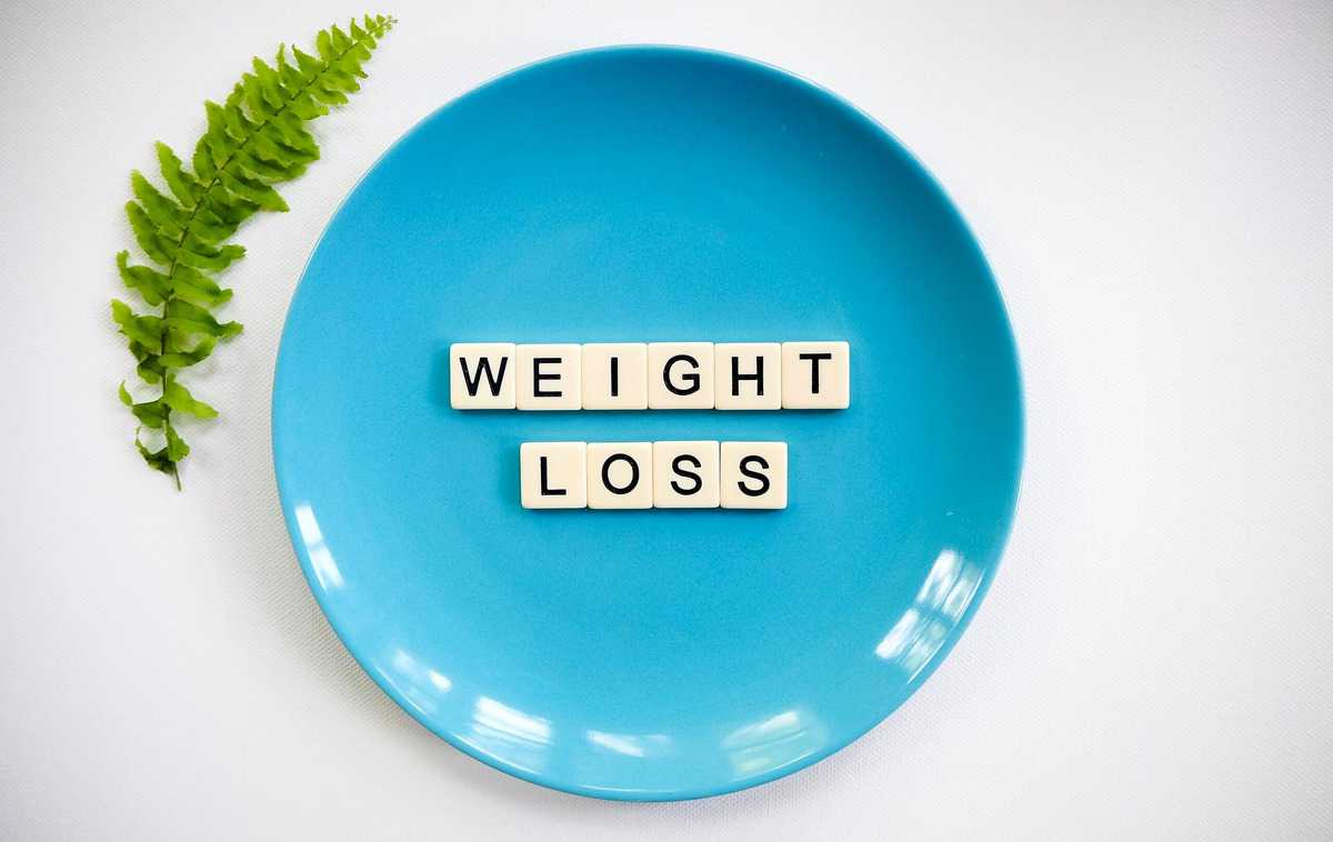"""Several tiles on a blue plate spelling """"weight loss""""."""