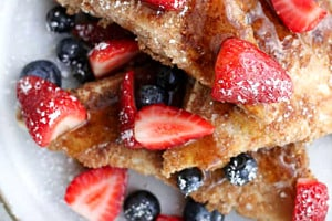 Overhead view of a plate of low carb french toast with powdered sugar and berries.