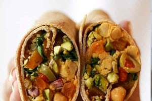 """Pinterest graphic of a half holding up a vegan chickpea salad wrap cut in half with the text overlay """"easy vegan recipe Moroccan chickpea wrap."""""""