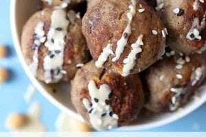 """Pinterest graphic of a bowl of toddler meatballs with tahini drizzle and text """"Toddler Meatballs With Hummus."""""""