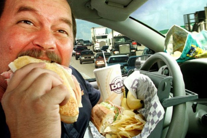 person eating fast food in a car