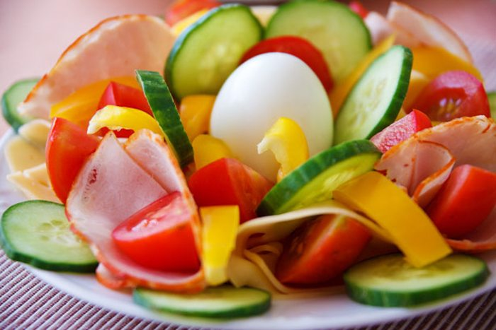 cut fruits and vegetables around an egg on a white plate