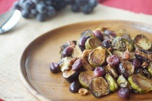 close up of balsamic roasted brussel sprouts with grapes and figs on a wooden plate