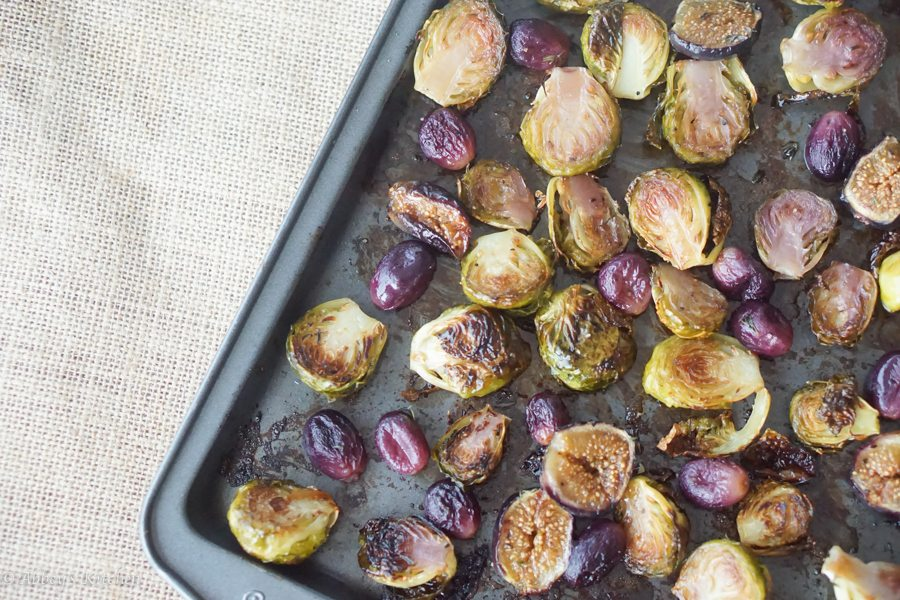 birds eye view of balsamic roasted brussel sprouts, figs, and grapes on a sheet pan
