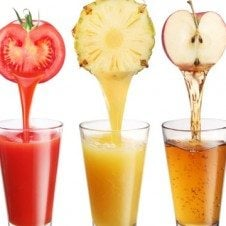Three glasses of juice with the corresponding produce over top: tomato, pineapple, and apple.