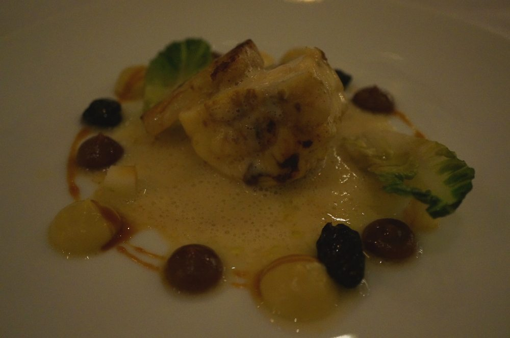 A plate of monkfish with grapes and apples.