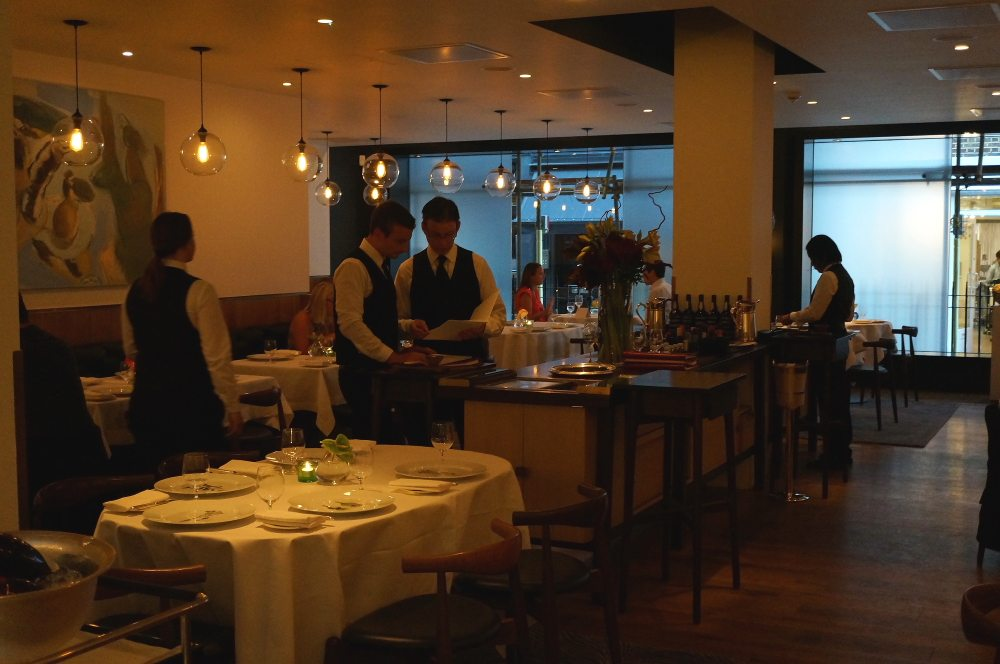 Inside of a restaurant with waiters standing.