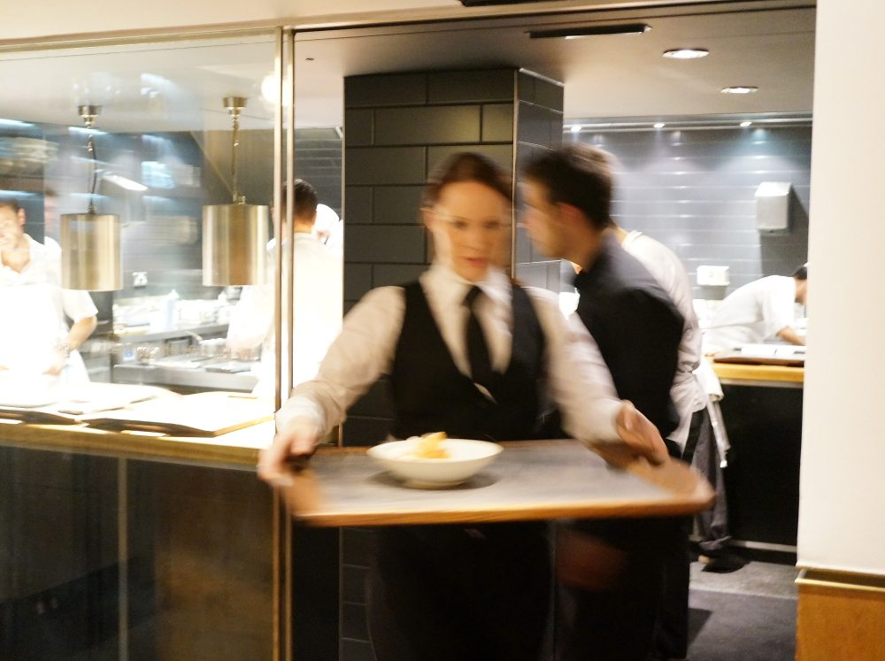 A waiter holding a tray of food in a kitchen.