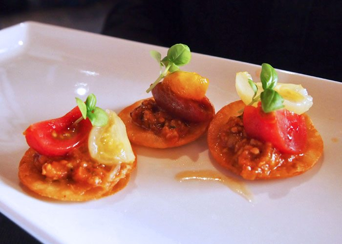 A set of three tomato appetizers on a plate.